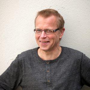 Bildet viser mann med brille og i grå genser, navnet hans er Per Kristian Alnes
